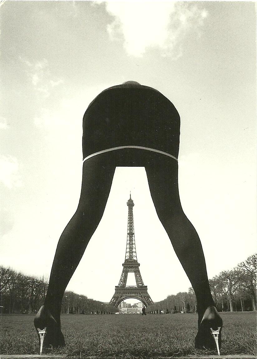 エッフェル塔を模したハイヒールシューズ(ピンヒールシューズ)を履いた女性が上半身を前方に屈めて、股下にエッフェル塔がくるように配置しています。